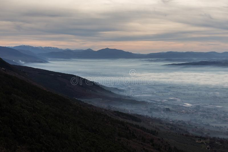 Beautiful aerial view of Umbria valley in a winter morning, with fog covering trees and houses , warm colors in the sky stock photography