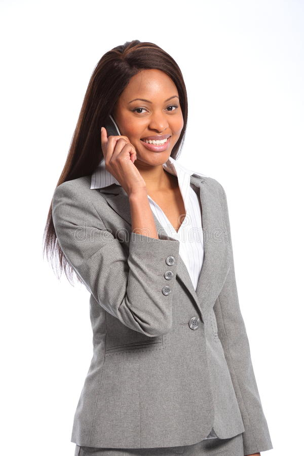 Beautiful african american business woman. Smiling young african american business woman looking confident and relaxed wearing grey suit, talking on the stock photo