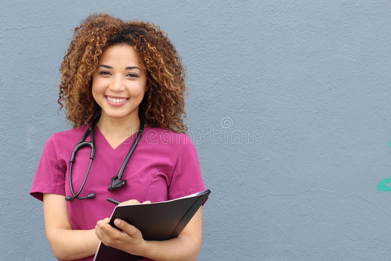 Beautiful african american female pediatric nurse holding pen and paper taking notes stock photography
