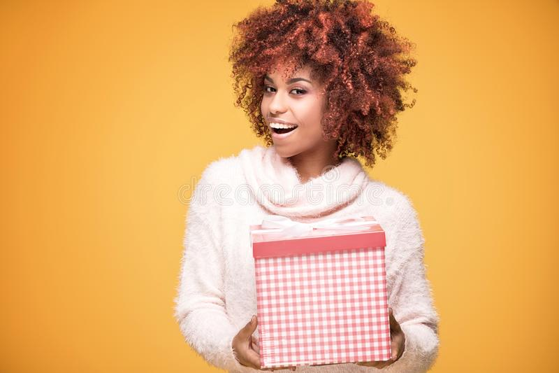 Afro girl posing with gift box, smiling. Beautiful african american girl with afro hairstyle holding gift box, smiling. Happy woman on yellow background royalty free stock photography