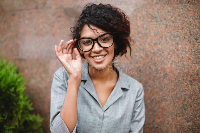 Beautiful African American girl in glasses happily looking in camera isolated. Smiling lady with dark curly hair sitting. Beautiful African American girl in royalty free stock photos