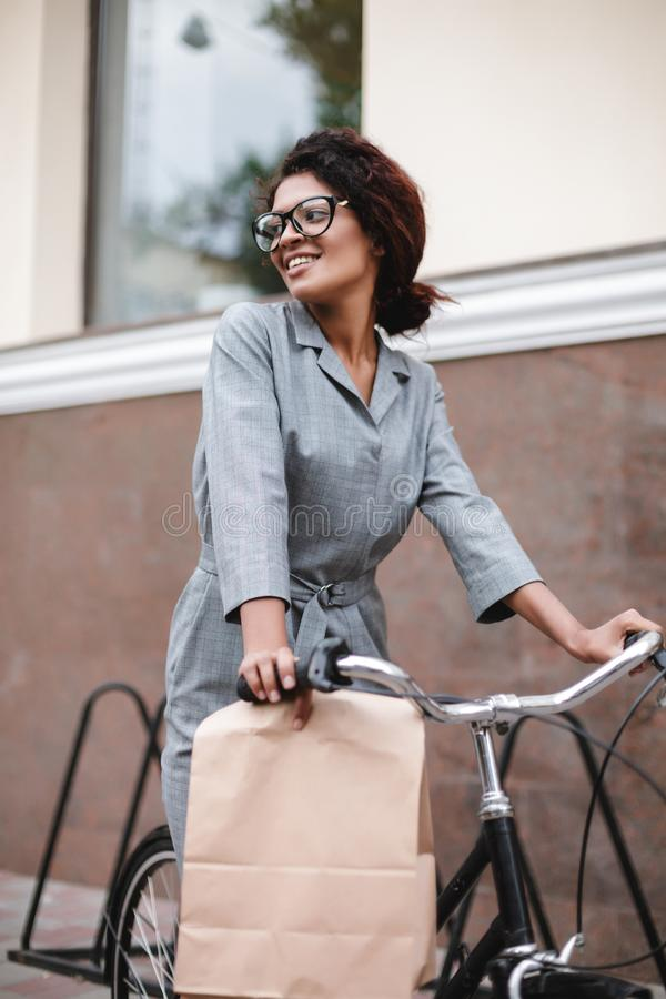 Beautiful African American girl in glasses riding on bicycle and dreamily looking aside. Young lady with dark curly hair. Beautiful African American girl in stock image