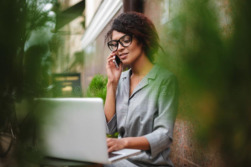 Beautiful African American girl in glasses sitting on bench and talking on cellphone dreamily looking in laptop. Young. Beautiful African American girl in royalty free stock photo