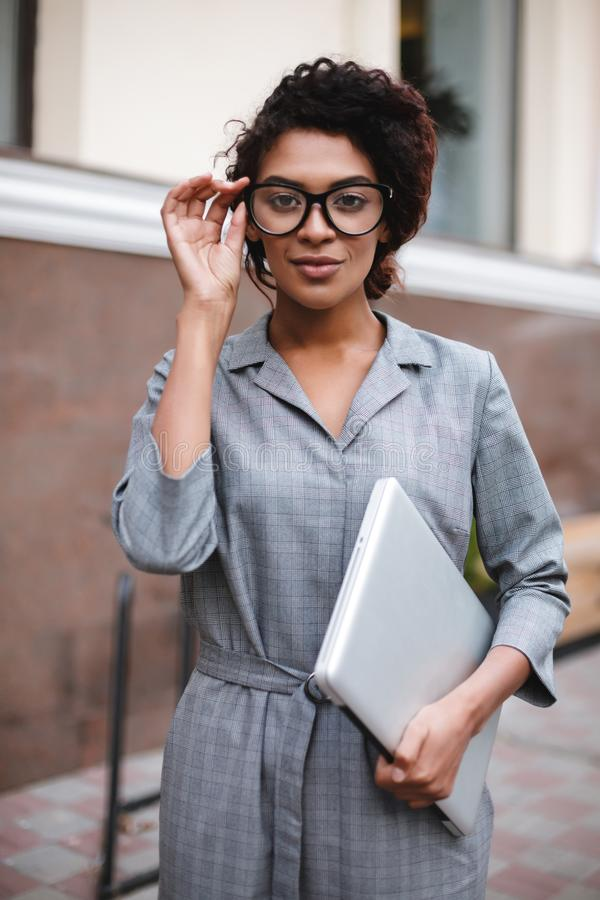Beautiful African American girl in glasses standing with laptop in hand and thoughtfully looking in camera. Young lady. Beautiful African American girl in stock image