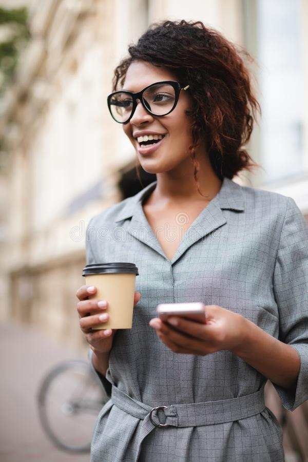 Beautiful African American girl in glasses standing on street with cellphone and coffee in hands while happily looking. Aside. Portrait of lady with dark curly royalty free stock image