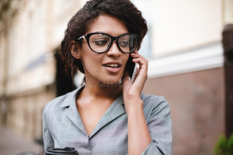Beautiful African American girl in glasses standing on street and talking on her cellphone. Lady with dark curly hair in. Beautiful African American girl in royalty free stock image