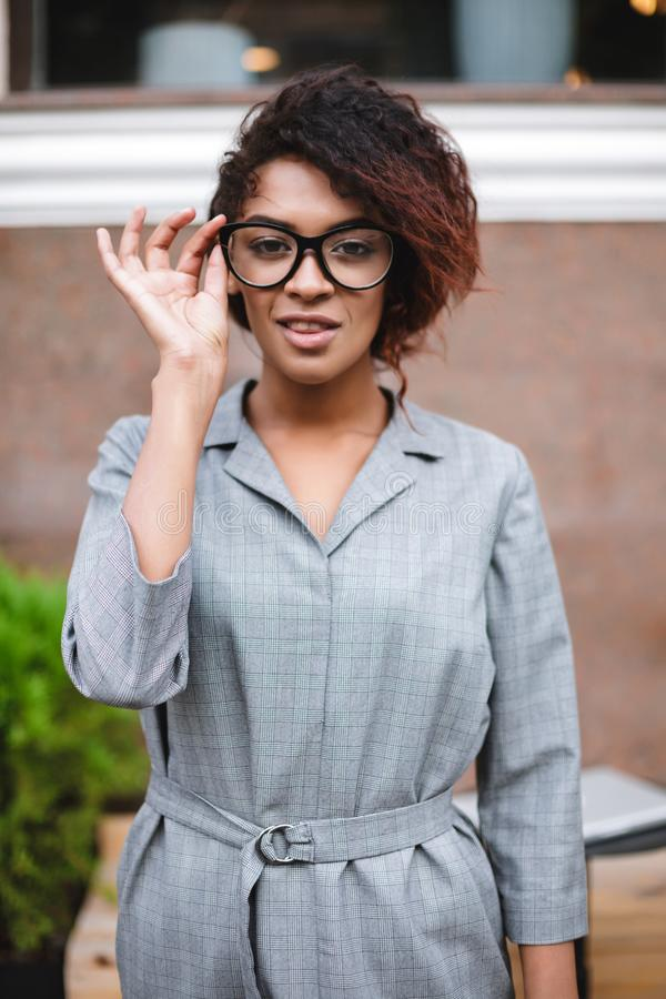 Beautiful African American girl in glasses standing on street and thoughtfully looking in camera. Young lady with dark. Beautiful African American girl in stock photo