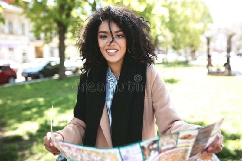 Beautiful African American girl happily looking in camera with map in hands. Nice girl standing on street and searching. Right way on map. Portrait of smiling stock photos