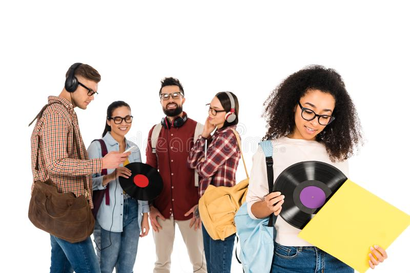 Beautiful african american girl standing with vinyl record near milticultural group of people in glasses isolated. On white stock photos