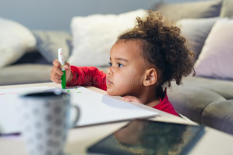 African American little girl drawing with colored pencils. stock photography