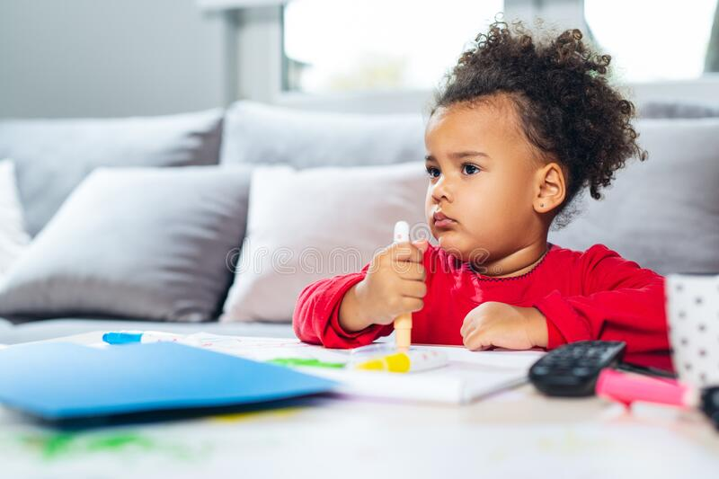 African American little girl drawing with colored pencils. stock photos