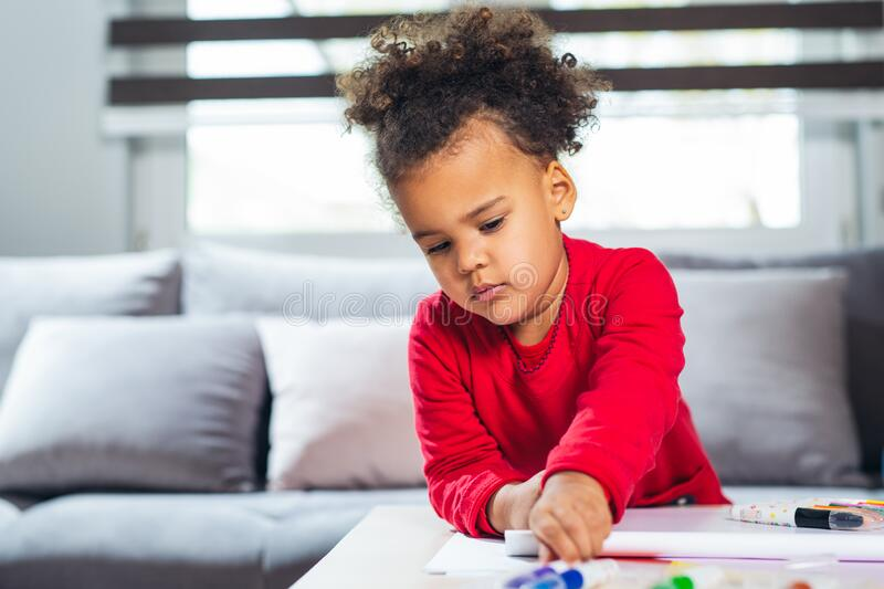 African American little girl drawing with colored pencils. stock photo