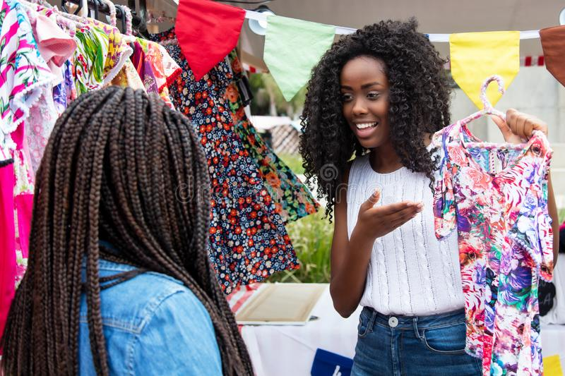 Beautiful african american market vendor presenting clothes to c. Beautiful african american market vendor presenting colorful clothes to customer at typical stock photos