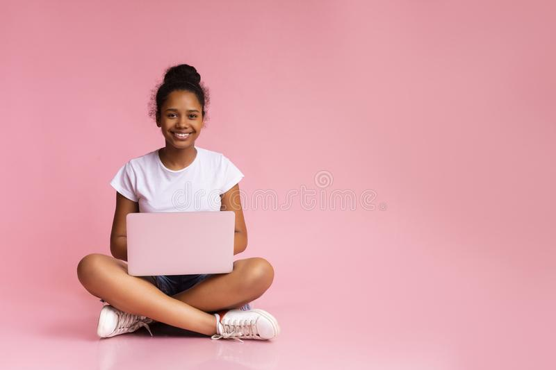Beautiful african girl sitting with laptop in lotus position. Beautiful african american teen sitting with laptop in lotus position on pink studio background royalty free stock photos