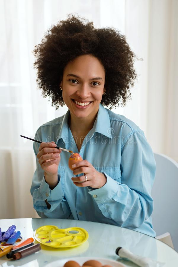 Beautiful African American woman coloring Easter eggs stock image