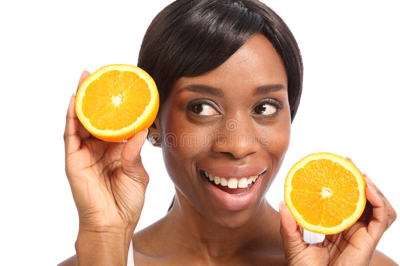 Beautiful african american woman healthy fruit. Healthy food promoted with happy smile with orange slice by beautiful young black woman royalty free stock images