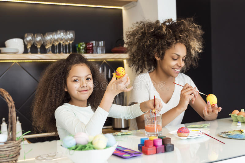 Beautiful African American woman and her daughter coloring Easter eggs in the kitchen stock photo