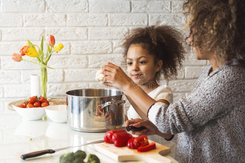 Beautiful African American woman and her daughter cooking. Beautiful African American women and her daughter cooking in the kitchen royalty free stock images