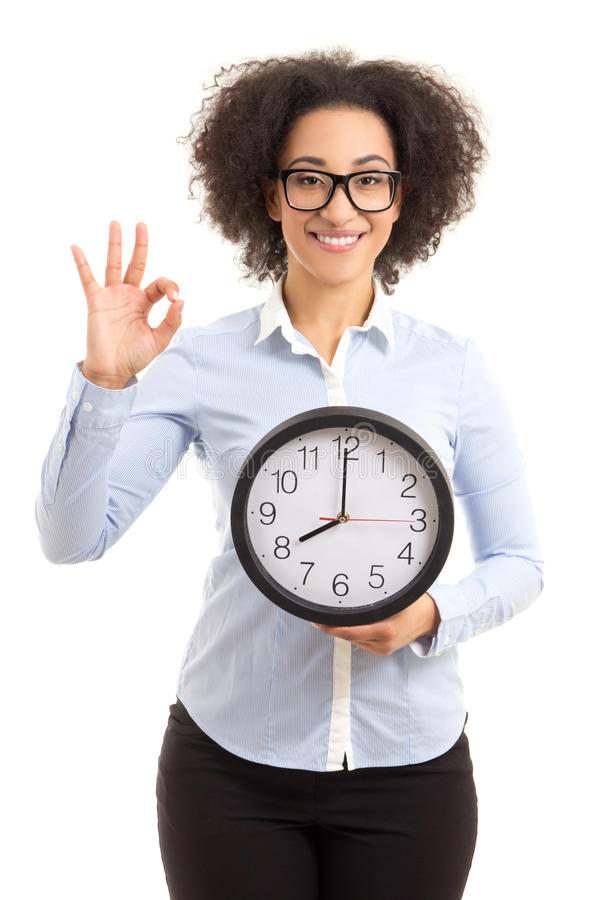 beautiful african american woman holding office clock and showing ok sign isolated on white stock photos