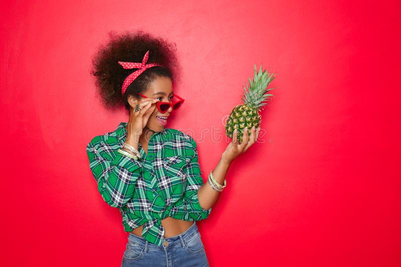 Beautiful African-American woman with pineapple on color background stock image