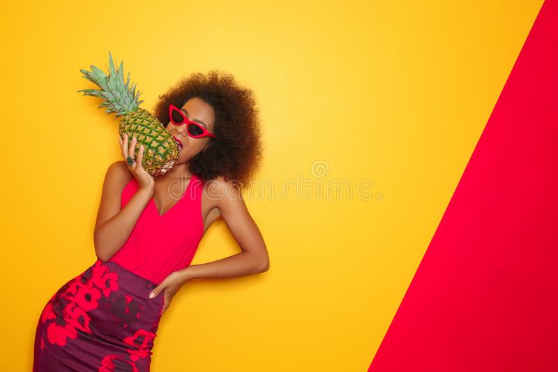 Beautiful African-American woman with pineapple on color background royalty free stock images