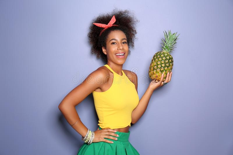 Beautiful African-American woman with pineapple on color background stock photography
