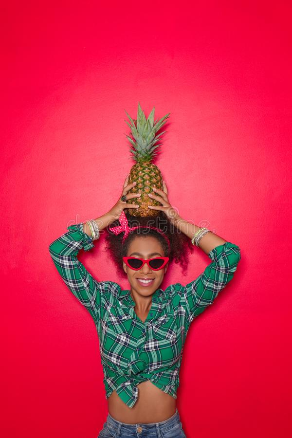 Beautiful African-American woman with pineapple on color background royalty free stock photography