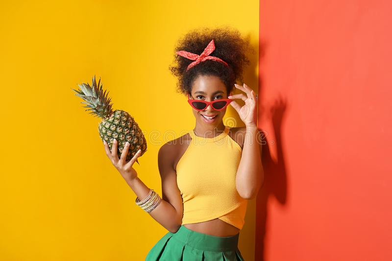 Beautiful African-American woman with pineapple near color wall stock images