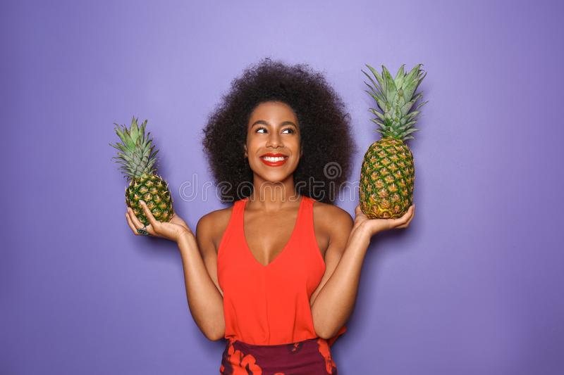 Beautiful African-American woman with pineapples on color background royalty free stock images