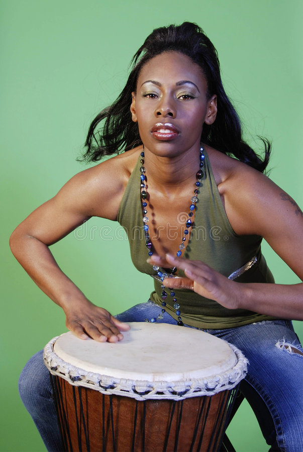 Beautiful African-American woman playing drums stock photography