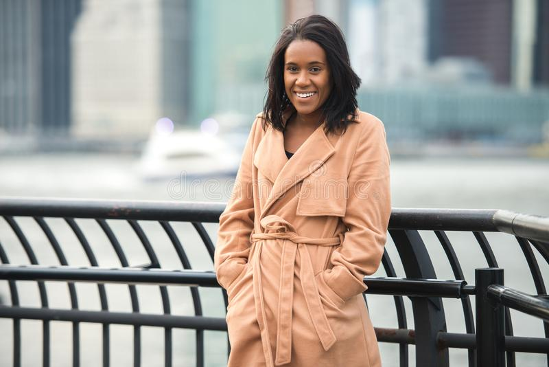 Beautiful african american woman smiling and looking in camera wearing cashmere jacket in the cold winter city. Beautiful african american woman smiling and royalty free stock image
