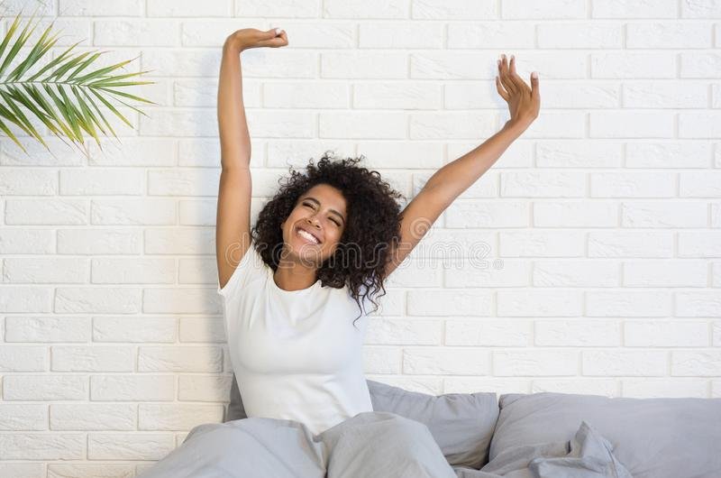 Beautiful black woman waking up in her bed. Beautiful african-american woman waking up in her bed, smiling and stretching, copy space stock photos