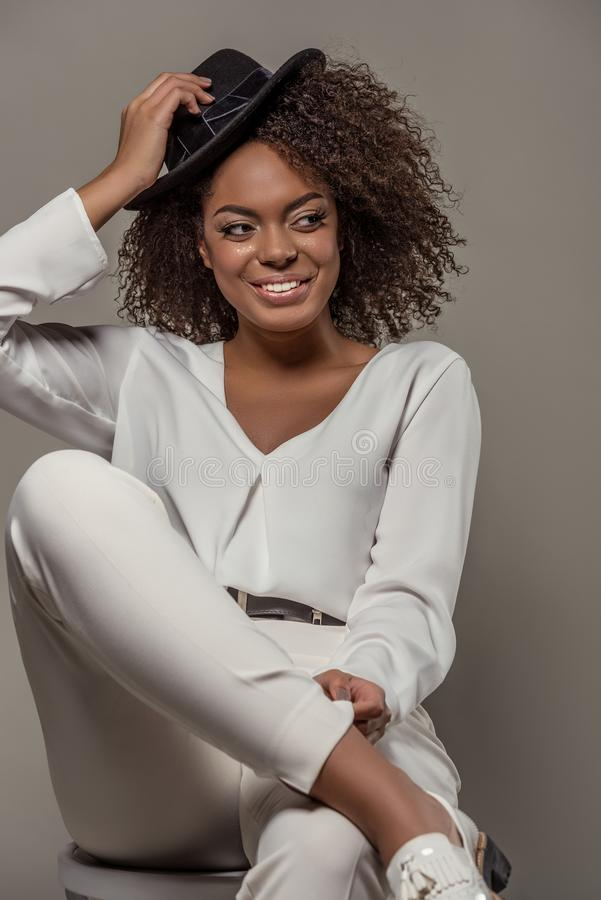 Beautiful african american woman in white clothes smiling and holding black hat royalty free stock photo