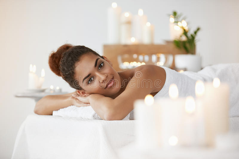 Beautiful african girl smiling looking at camera resting relaxing in spa salon. royalty free stock image