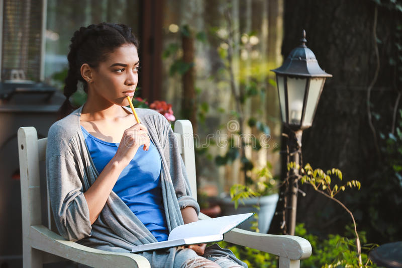 Beautiful african girl writing at the notebook royalty free stock photography