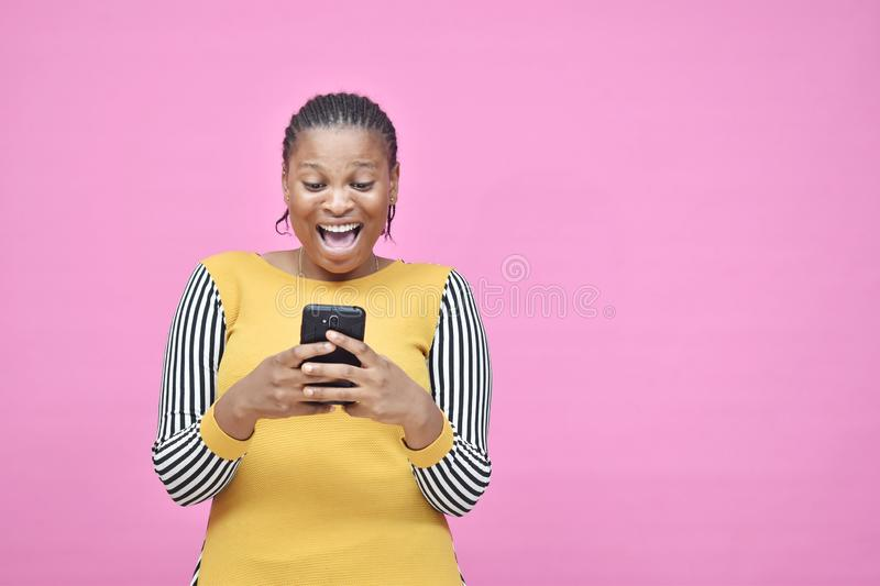 beautiful african lady using her smartphone looking surprised and excited while viewing content on her phone royalty free stock images