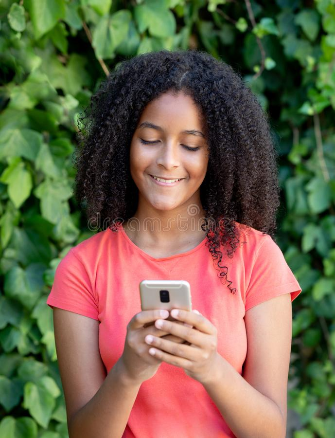 Beautiful teenager girl with a mobile. Beautiful african teenager girl with a mobile in a park royalty free stock photography