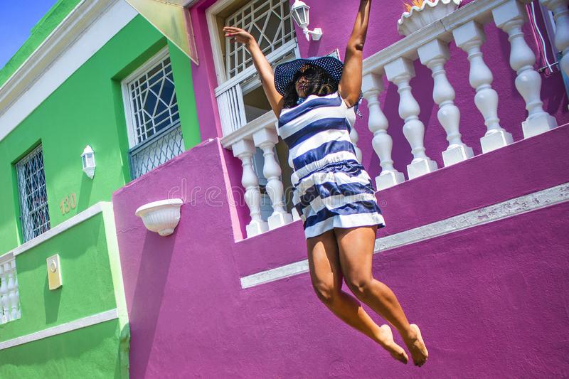 A beautiful African woman in a blue and white striped dress jumping in front of traditional homes with pink and green walls. Bo-Ka. Bo-Kaap - Sightseeing stock images