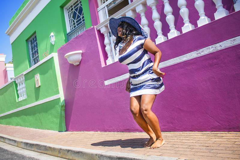 A beautiful African woman in a blue and white striped dress jumping in front of traditional homes with pink and green walls. Bo-Ka. Bo-Kaap - Sightseeing royalty free stock photography