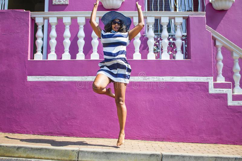 A beautiful African woman in a blue and white striped dress jumping in front of traditional homes with pink and green walls. Bo-Ka. Bo-Kaap - Sightseeing stock photos
