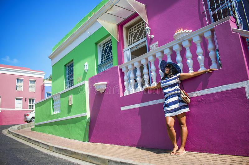 A beautiful African woman in a blue and white striped dress modelling in front of traditional homes with pink and green walls. Bo-. Bo-Kaap - Sightseeing stock image