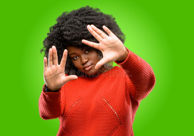 Beautiful african woman with curly hair isolated over green background. Beautiful african woman confident and happy showing hands to camera, composing and royalty free stock photo