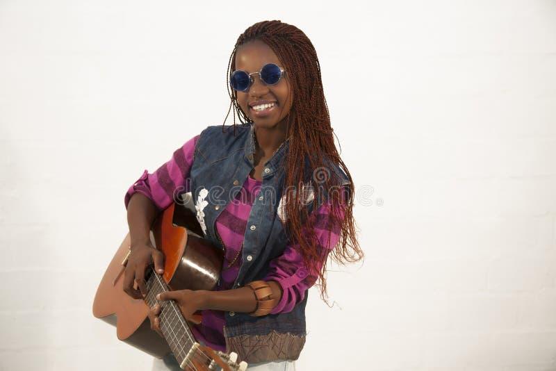 Beautiful african woman playing guitar stock photography