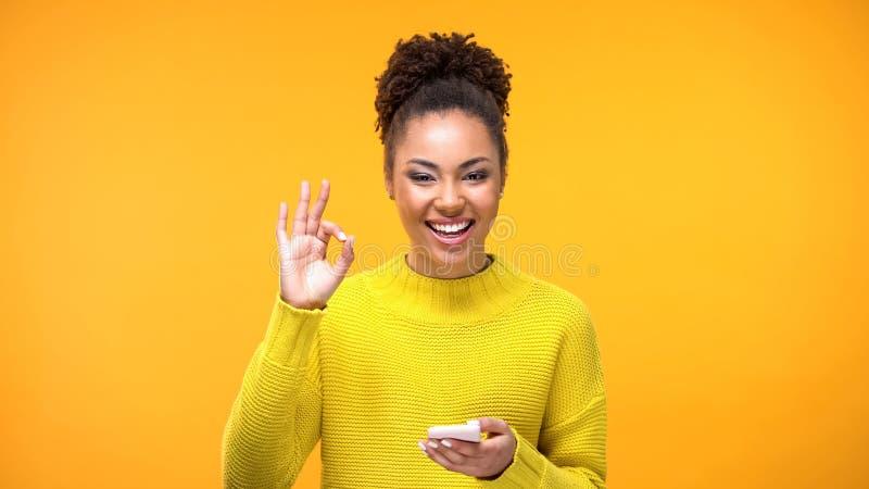 Beautiful african woman showing ok gesture, online shopping application, gadget stock photos