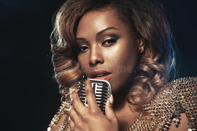 Beautiful African woman singing stock photo