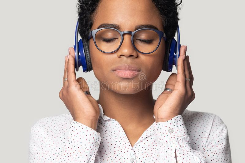Beautiful african woman wearing headphones listen favourite music studio shot stock photography