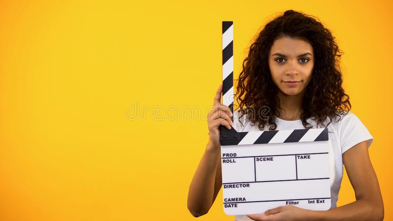 Beautiful afro-american woman holding clapper board, movie shooting, audition stock image