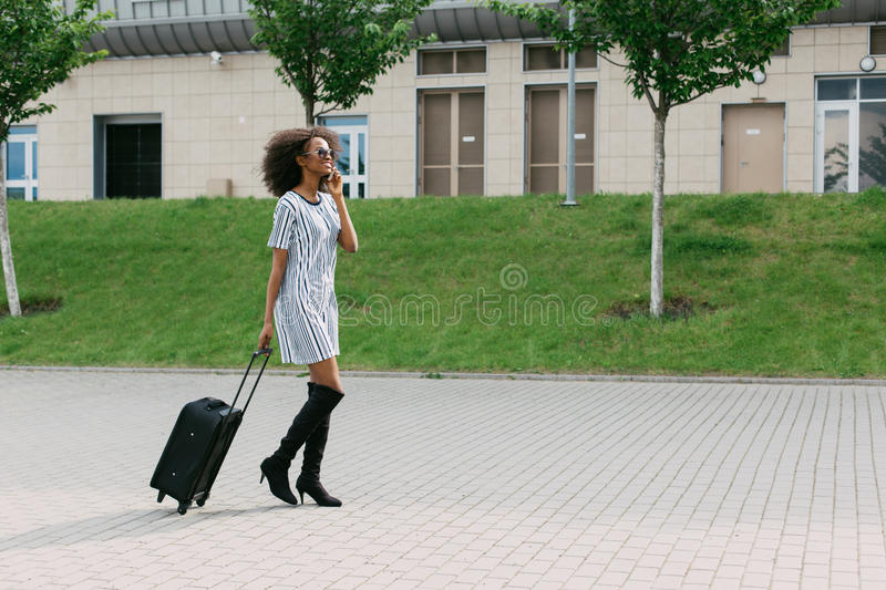 Beautiful afro-american woman is talking via the mobile phone while holding the luggage. Beautiful afro-american woman is talking via the mobile phone while royalty free stock photography
