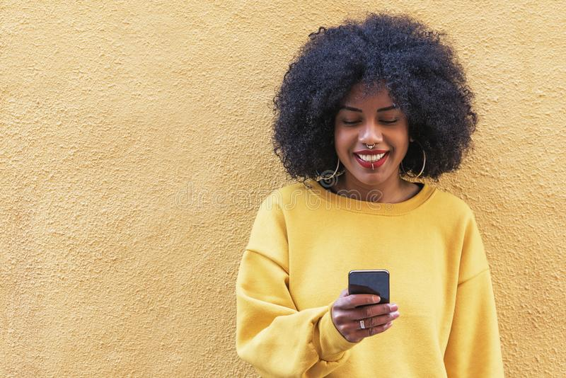 Beautiful afro american woman using mobile in the street. royalty free stock image