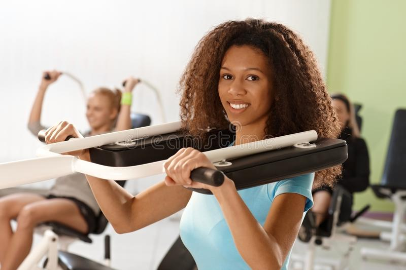 Beautiful afro woman training on weight machine. Beautiful young afro women training at gym using weight machine, smiling stock photos